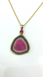 Tourmaline cut to look like a watermelon made as a pendant for jewelry.